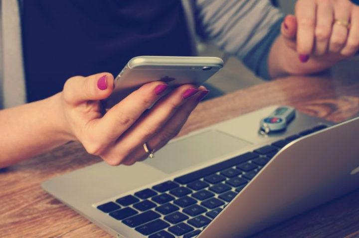Мобильный в руках у девушки, ноутбу на столе