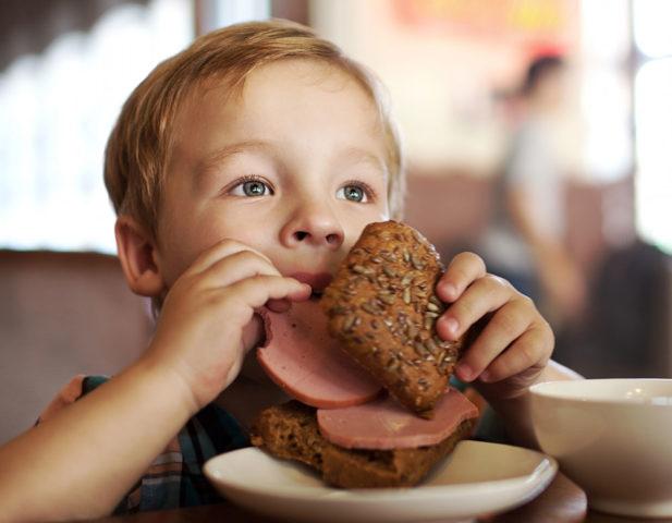 Ребенок ест колбасу