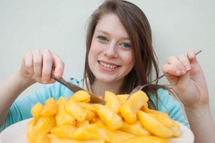 Женщина ест картошку