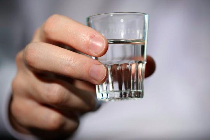 Стопка водки в руке