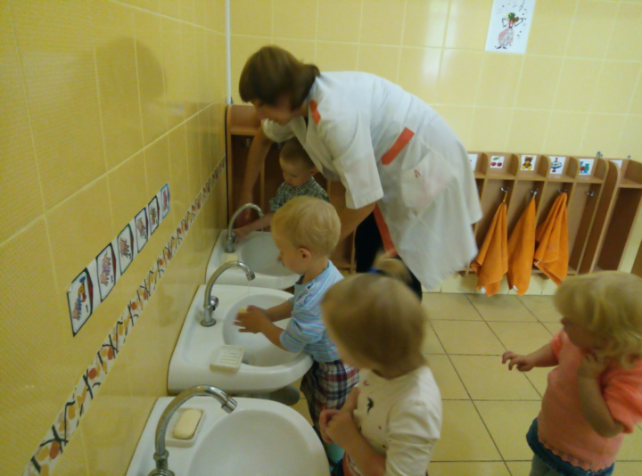 Дети и младший влспитатель в детском саду