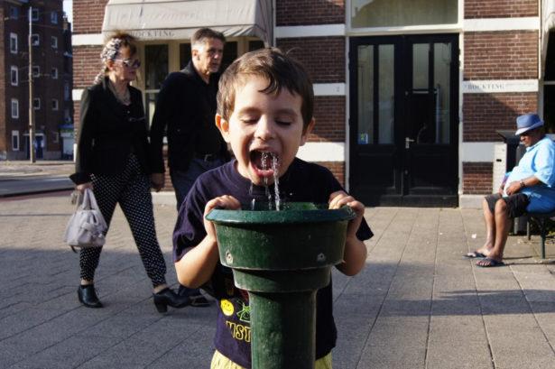 Ребенок пьет с фонтанчика