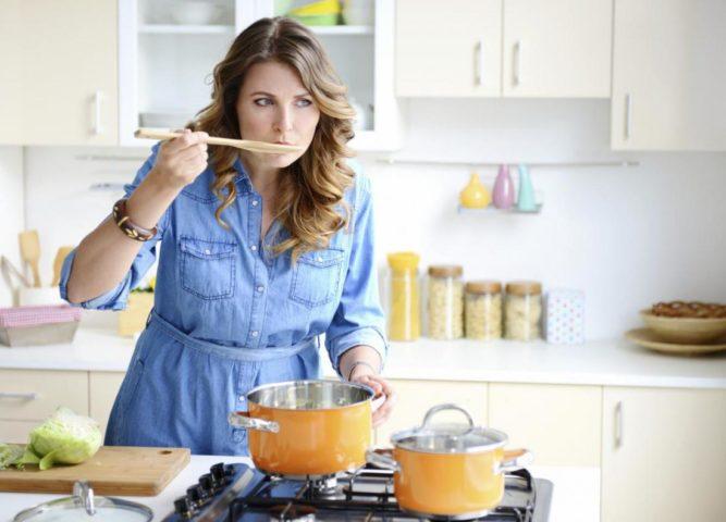 Девушка пробует еду при готовке