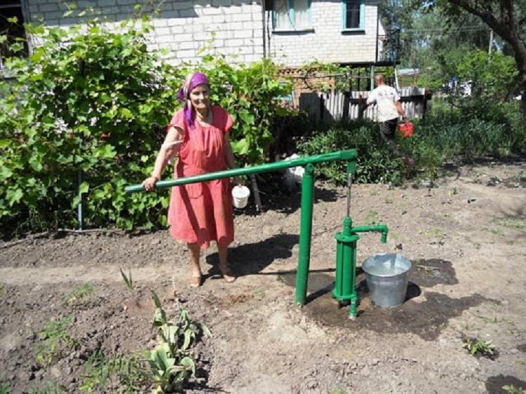 Пожилая женщина и скважина с водой