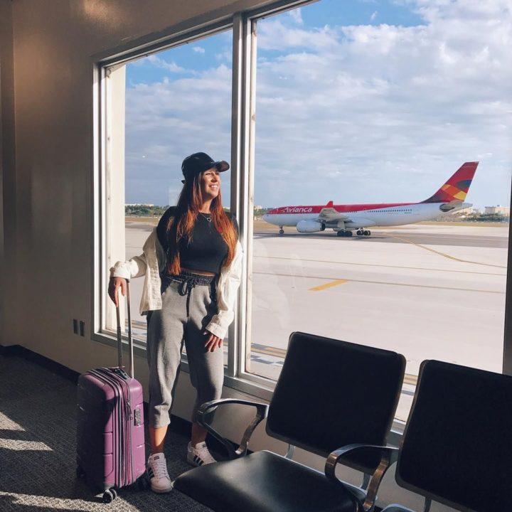 Девушка с чемоданом в аэропорту