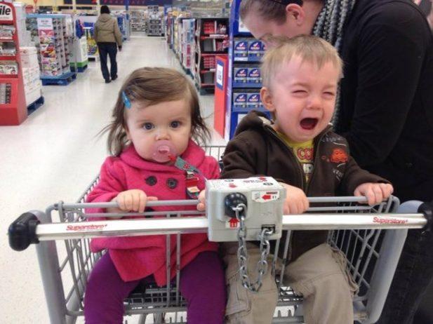 Девочка и мальчик в тележке с сидениями для детей