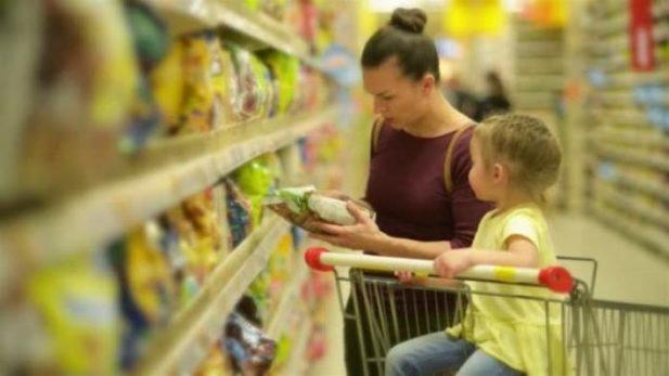 Женщина с ребенком у стеллажа в супермаркете