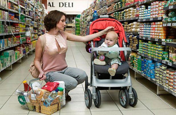 Женщина и маленький ребенок в коляске в суермаркете