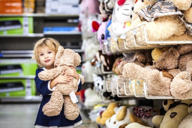 Девочка с игрушечным мишкой в супермаркете