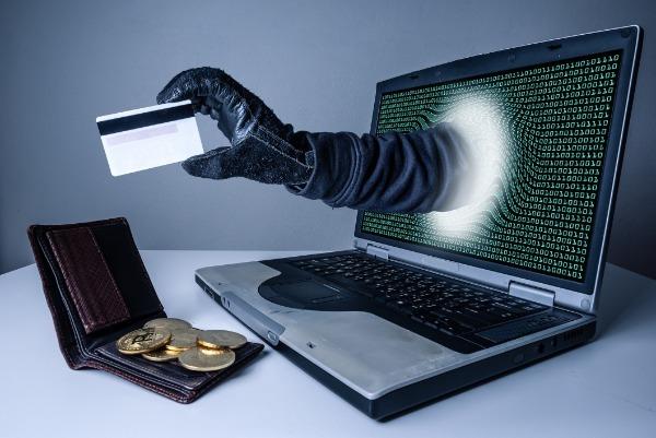 Рука из ноутбука с банковской картой