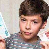 Мальчик держит рубли в руках