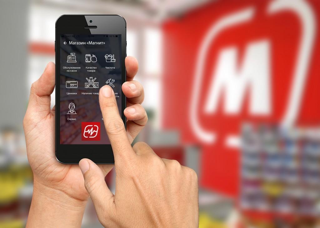 """Смартфон в руке с установленным приложением сети """"Магнит"""""""