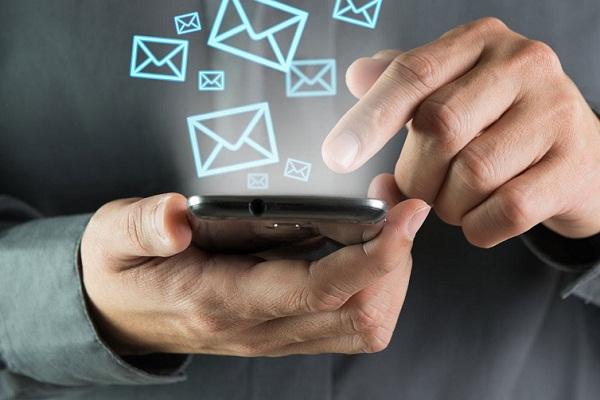 Смартфон в руках и вылетающие из него виртуальные конверты
