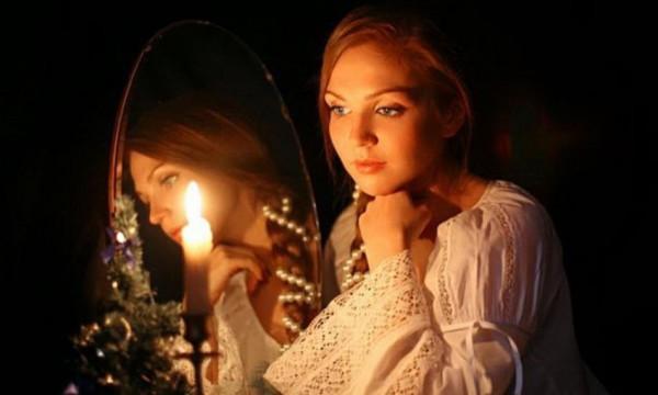Девушка перед зеркалом со свечой в полной темноте