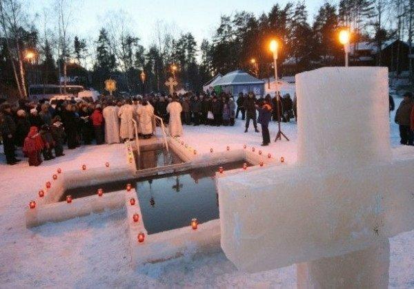 Крещенская прорубь, люди и ледяной крест на переднем плане