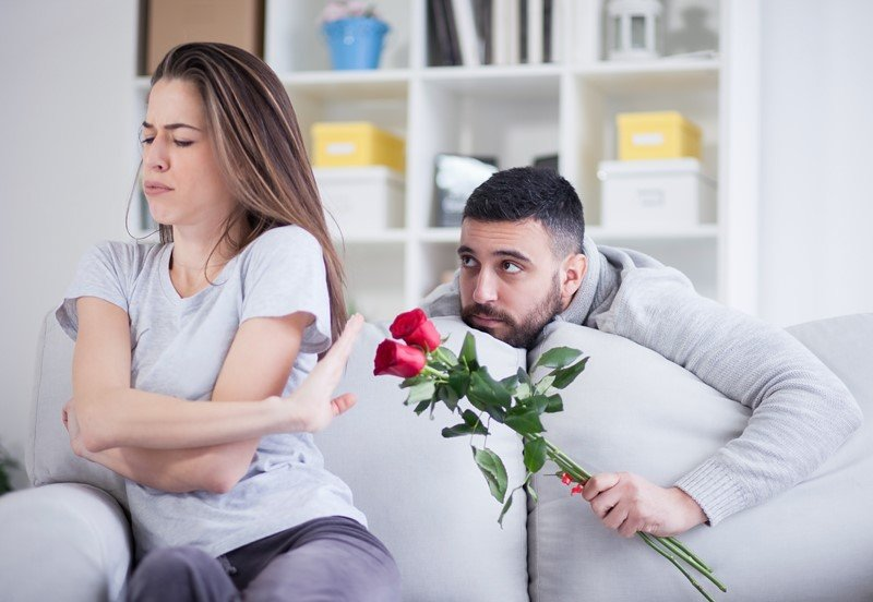 Обиженная девушка и преподносящий ей букет роз молодой человек