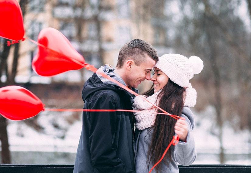 Пара обнимается и держит шарики в виде сердечек