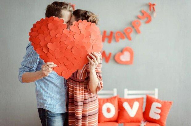 Влюбленные прячутся за большой валентинкой, сделанной из множества сердечек