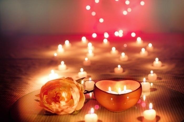 Живя роза и множество зажженных свечей
