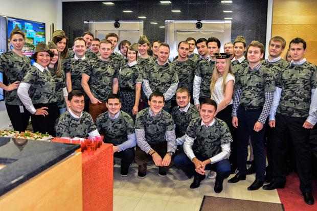 Рабочий коллектив в одинаковых футболках хаки в офисе