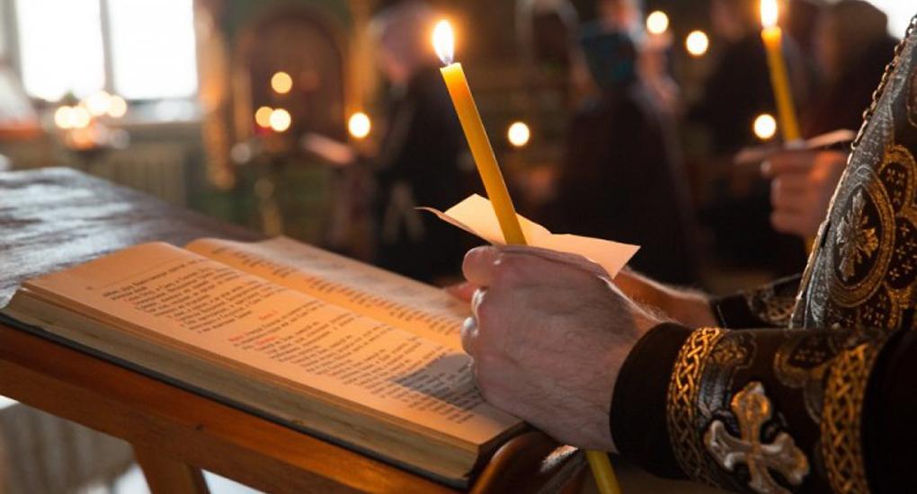 молитвослов и руки священнослужителя со свечой над ним