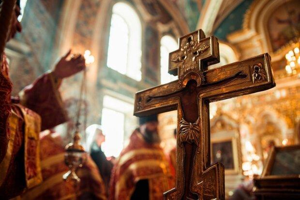 Святое распятие в церкви и священнослужитель с ладаном на фоне