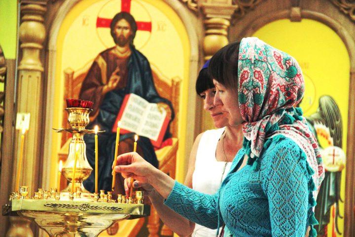 Женщины ставят свечи в церкви