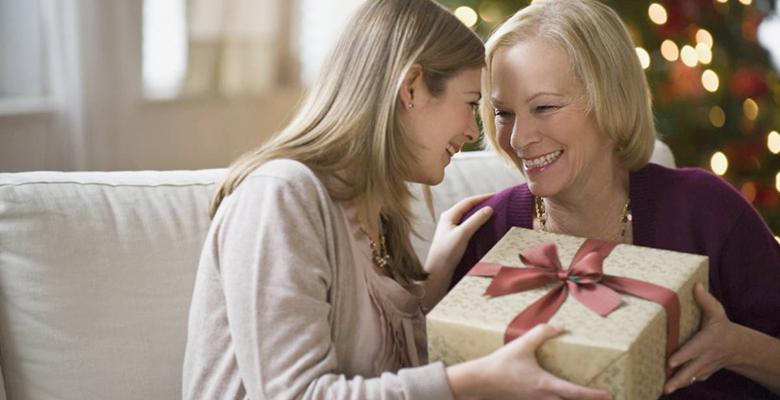 Дочка и мама смеются, держа в руках подарок
