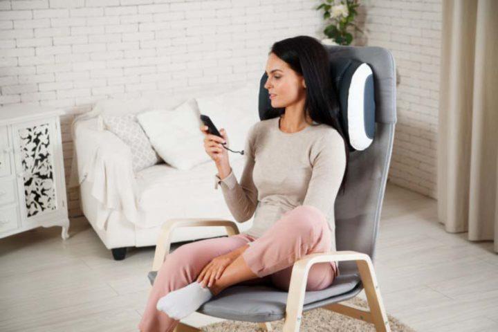 Девушка сидит на кресле с массажной подушкой