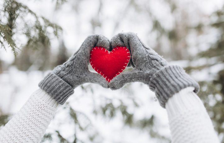 Сердечко в руках на фоне заснеженного пейзажа
