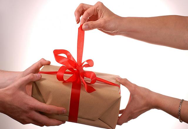Подарок с красным бантом из рук в руки