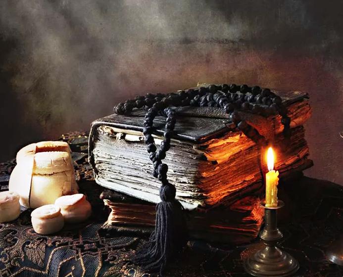 Старинное священное писание, четки, просвирки и горящая свеча на столе