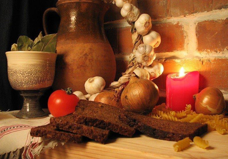 Черный хлеб, овощи, горящая свеча и кувшин