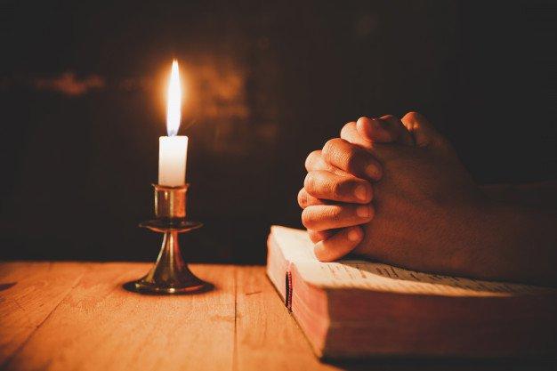 Руки на молитвослове и горящая свеча