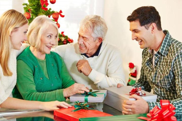 Пожилая и молодая пара распаковывают подарки