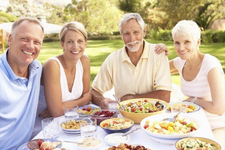 Люди в возрасте за праздничным столом на свежем воздухе