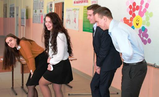 Старшеклассники смеются в школьном коридоре