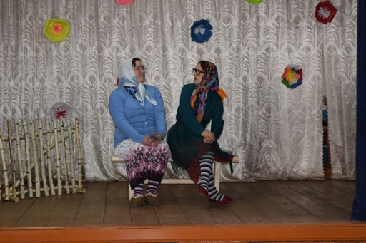 Две ряженые бабушки на сцене сельского клуба
