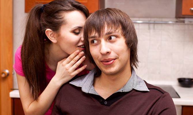 Девушка шепчет парню что-то на ушко