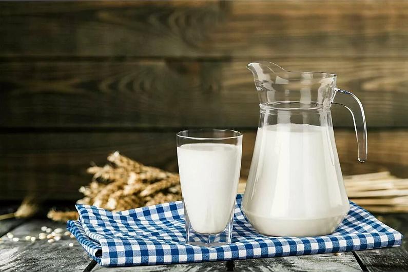 Кувшин и стакан с молоком на клетчатой скатерти
