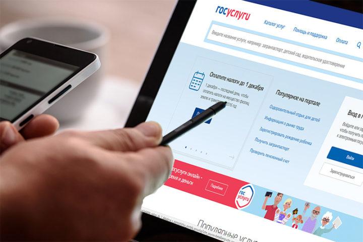 Открытый на планшетном ПК сайт Госуслуг и рука со стилусом