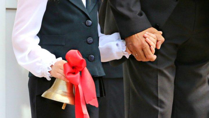 Школьница с колокольчиком держит за руку взрослого человека в костюме