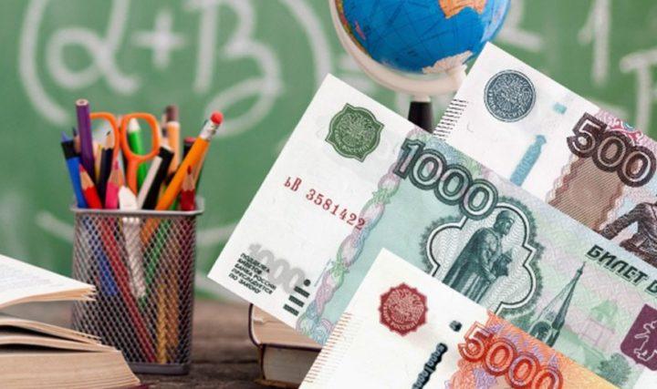 Рубли на фоне канцелярии, глобуса и школьной доски