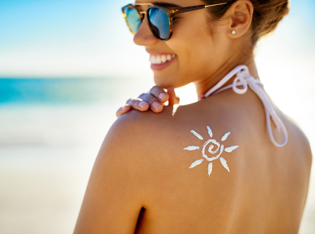 Девушка на пляже улыбается солнышку из солнцезащитного крема на своей спине