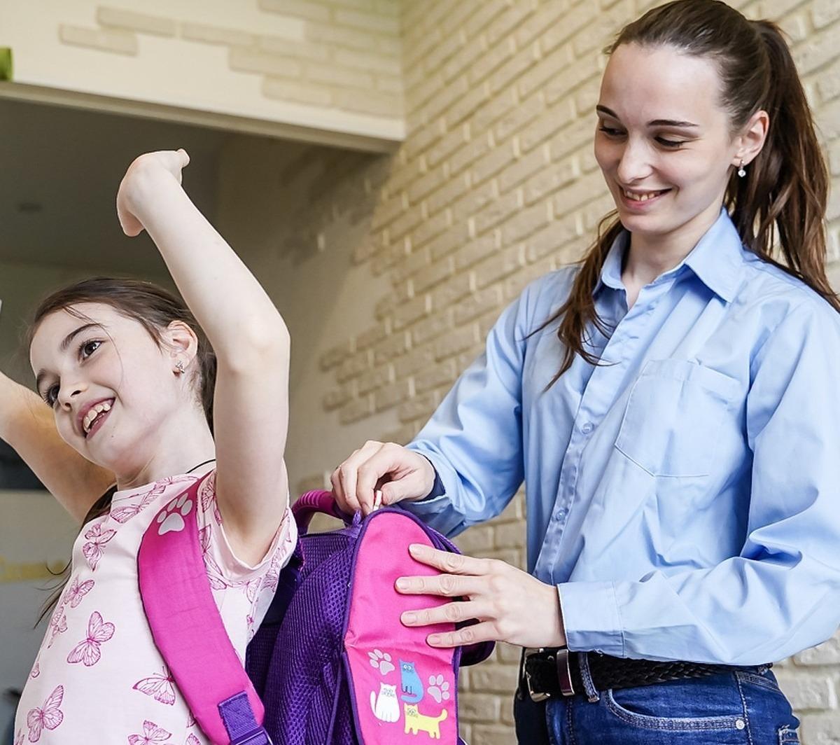 Мама собирает дочку в школу, поправляя рюкзак на ее спине