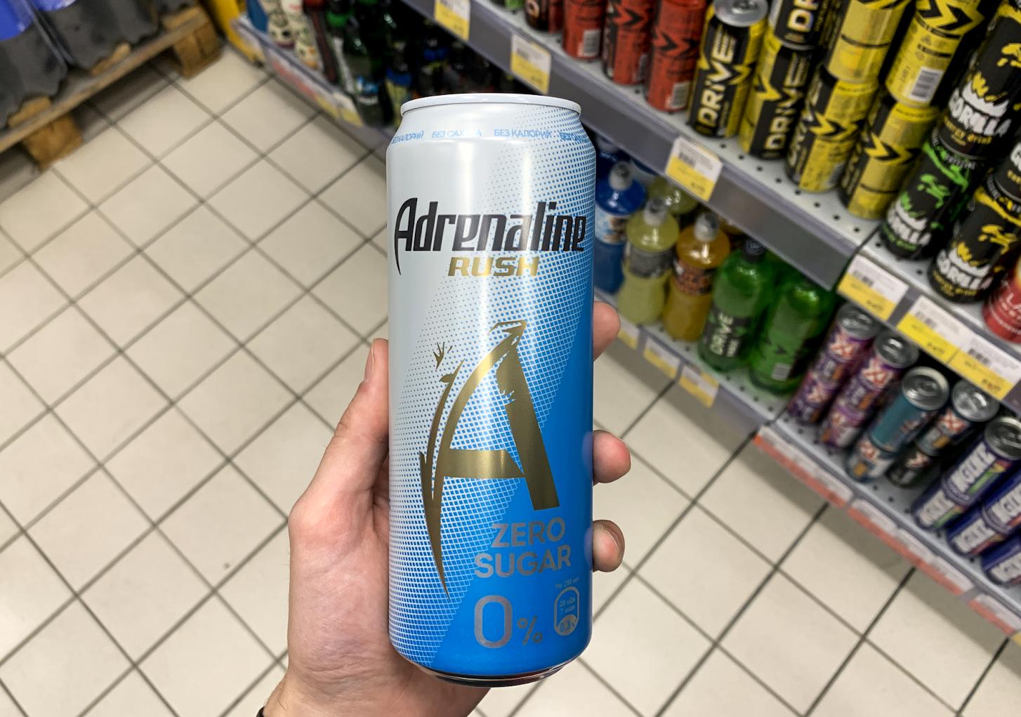 Энергетик в банке Adrenaline Rush без сахара в руке покупателя