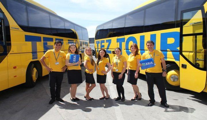 Сотрудники TezTour на фоне автобусов компании