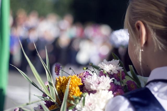 Девочка на 1 сентября с букетом спиной к объективу