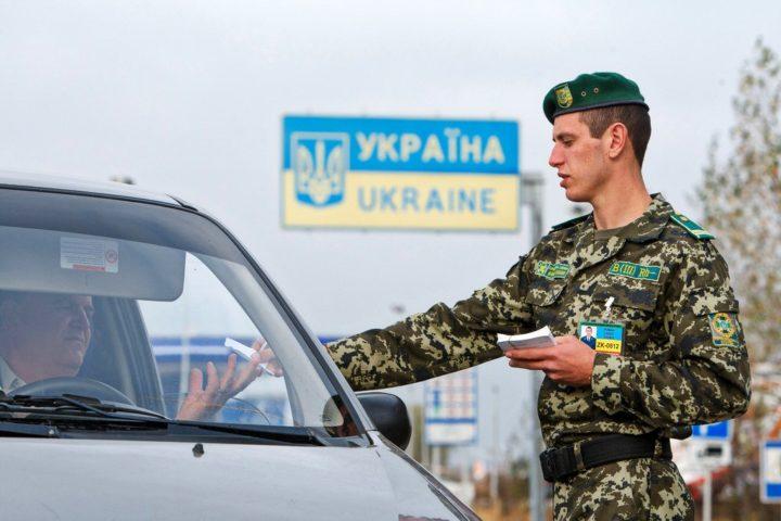 Пограничник проверяет документы у водителя на украинской таможне