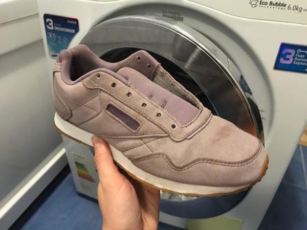 Спортивная обувь в руке на фоне стиральной машины